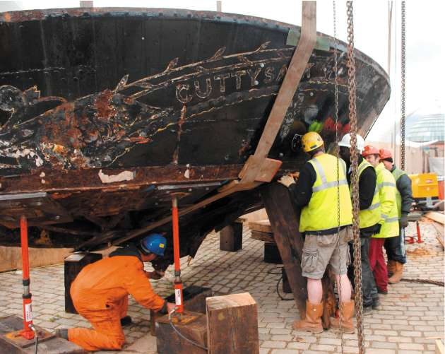 Workmen continue to restore the Cutty Sark after fire nearly destroyed the ship last year