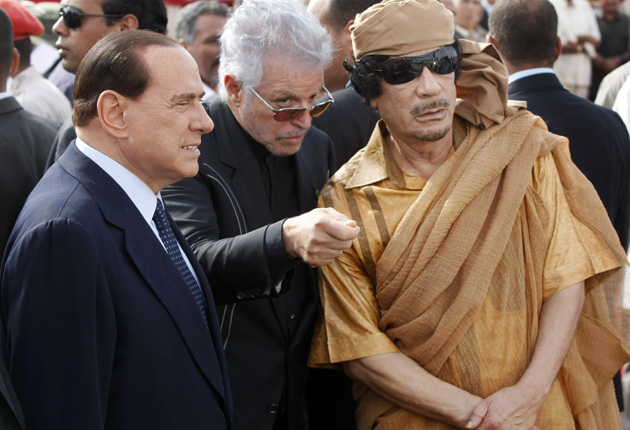 Then Italian prime minister Silvio Berlusconi and Muammar Gaddafi attend a ceremony to lay the first stone of a new Italian-funded highway, in Tuweisha, Libya, in 2009