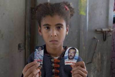 Amal Samouni, aged 10, holds photos of her father and brother, both killed by Israeli troops
