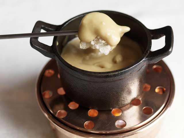 Serve the fondue on a table heater with the chunks of bread separately using long forks or skewers