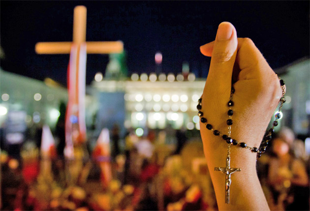 A woman holds a rosary during a rally