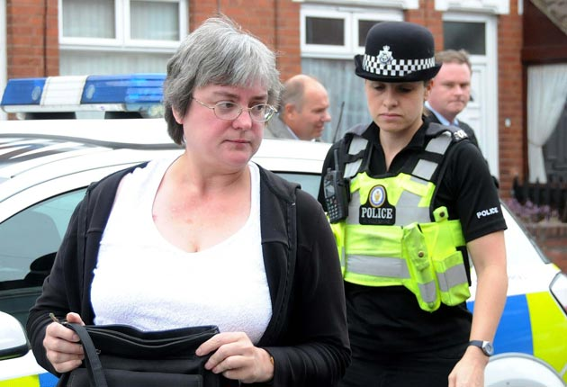 Ms Bale is escorted by police to her front door after an online campaign led to national press outrage and death threats