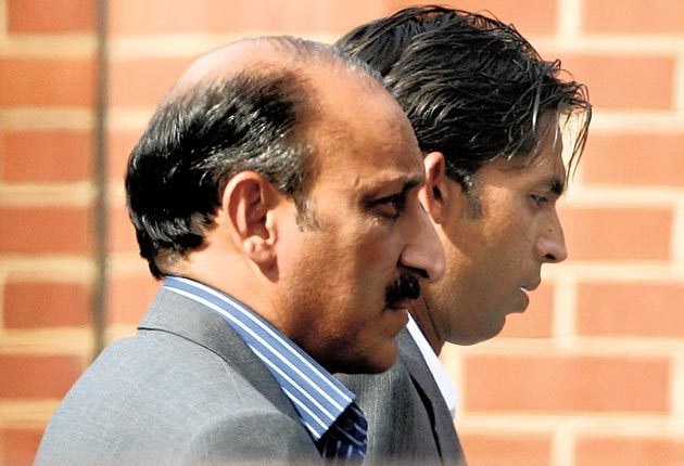The Pakistan bowler Mohammad Asif, right, arrives with an unidentified man at a police station