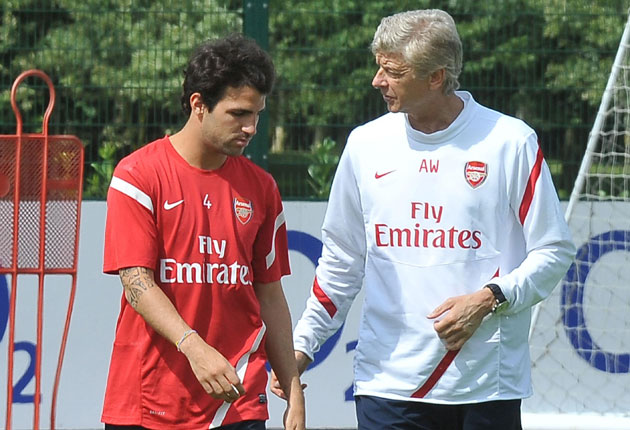Cesc Fabregas (left), with Arsène Wenger, is not in Arsenal's squad to play Benfica