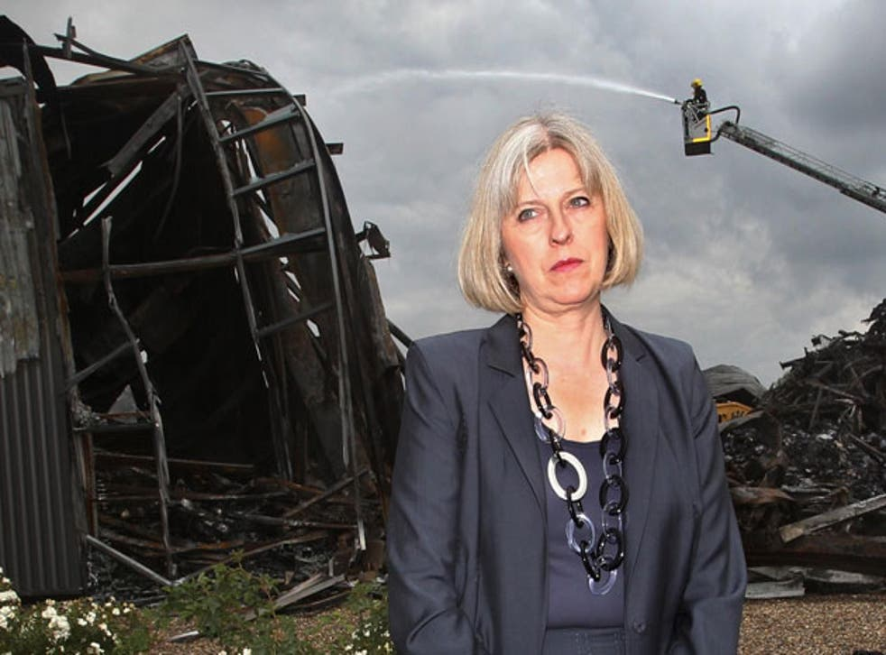 The Home Secretary, Theresa May, visits the burnt-out remains of a Sony distribution warehouse in Enfield yesterday