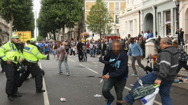 In an extraordinary picture, the young man, left of centre, wearing faded jeans and a red and white stripey top, looks astonished as he realises he has been stabbed in the abdomen and hand.