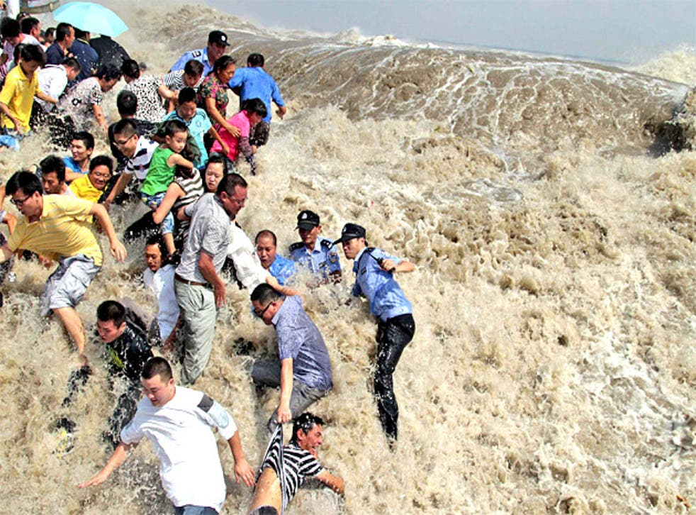 Residents and police run for their lives as a tidal wave bursts the banks of the Qiantang River in Zhejiang province