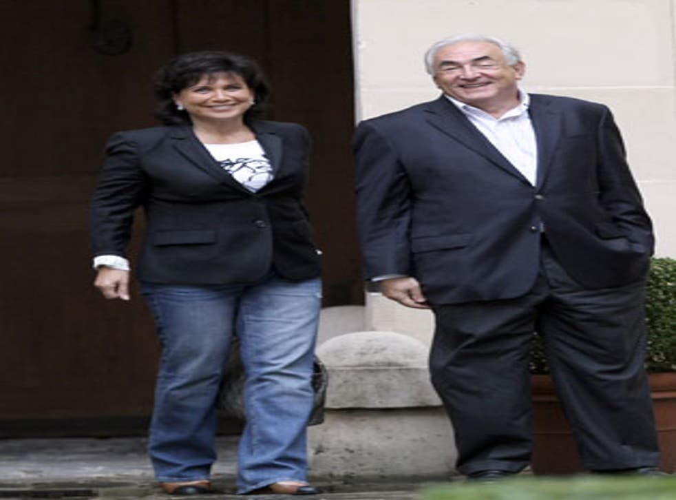 Dominique Strauss-Kahn and his wife, Anne Sinclair, in the courtyard of their Paris home yesterday