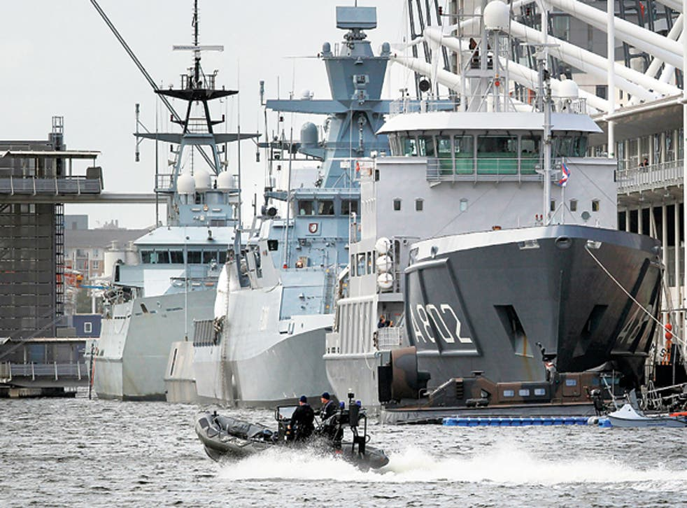 A police boat passes naval vessels at the ExCeL centre