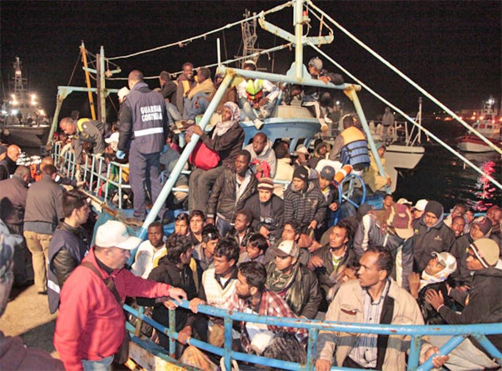 Italian coastguards look on as African refugees arrive on Lampedusa