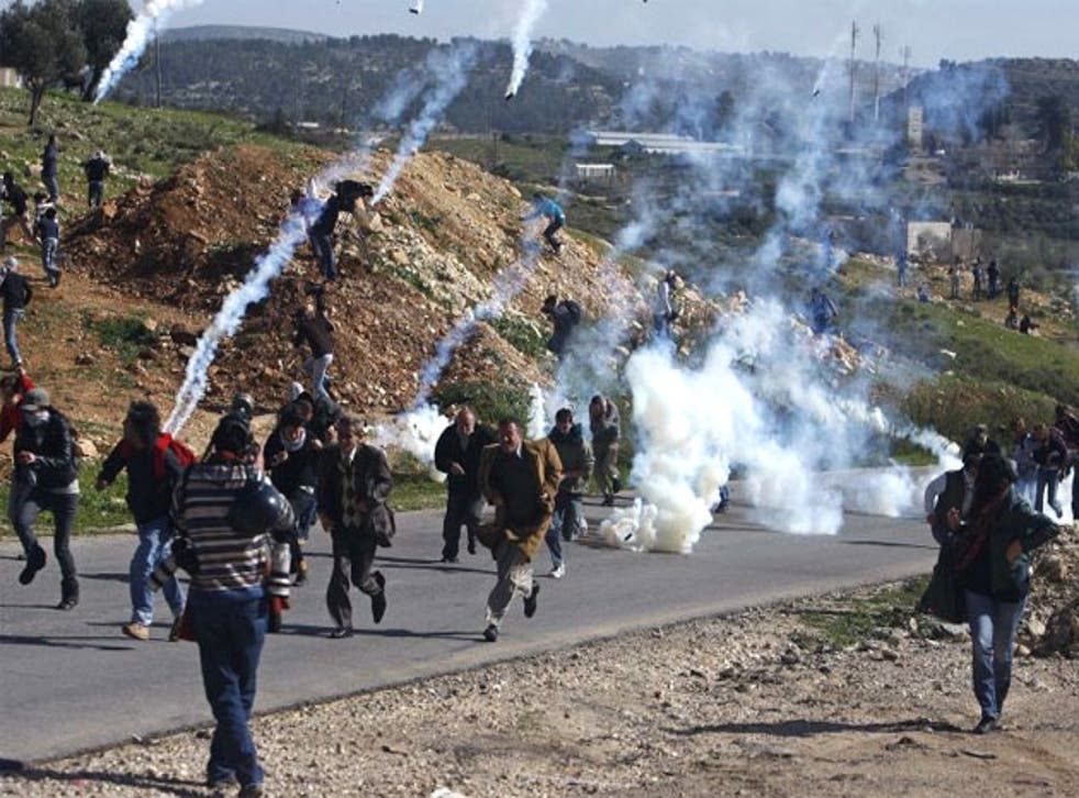 Palestinian protesters run from tear gas fired by Israeli troops in Nabi Saleh in January 2010