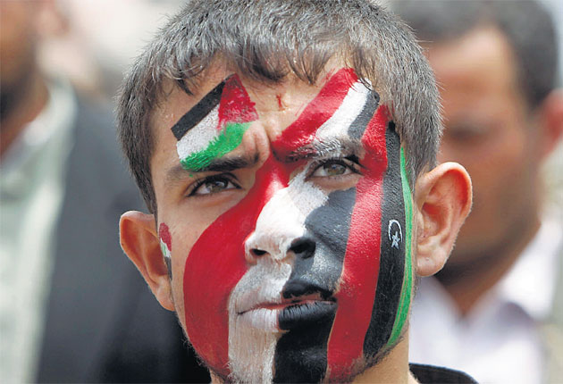A protester in the Yemeni capital, Sanaa, wears the colours of Syria, Libya, Yemen and the Palestinians