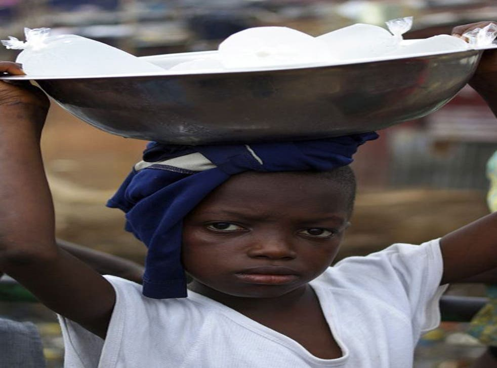 Sorie Sesay, 10, carries packets of water to sell in Freetown