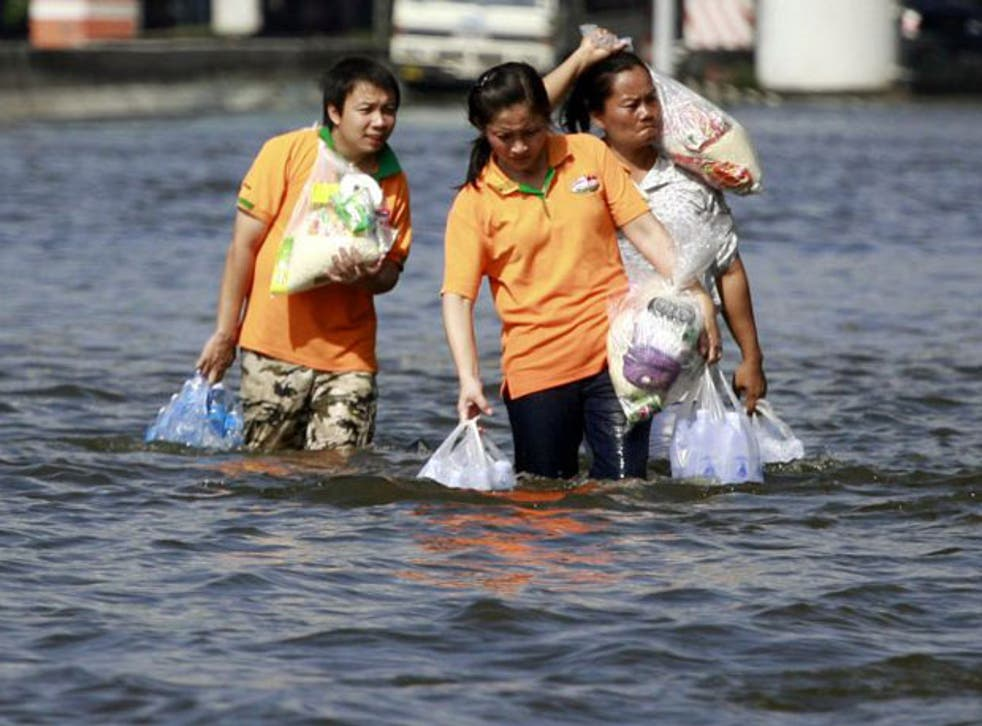 Residents carrying relief packages wade through a flooded street  in Bangkok