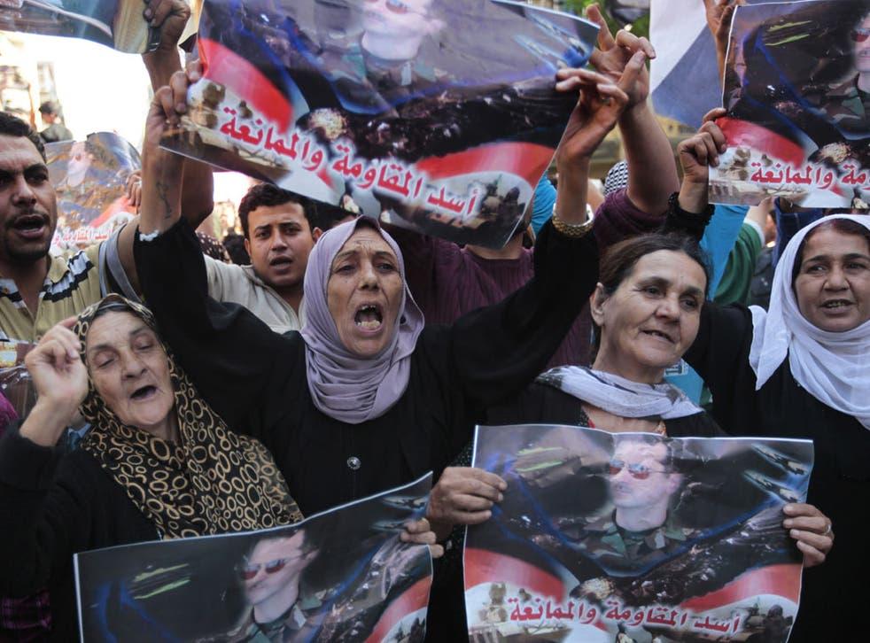 Pro-regime protesters hold up posters of Bashar al-Assad