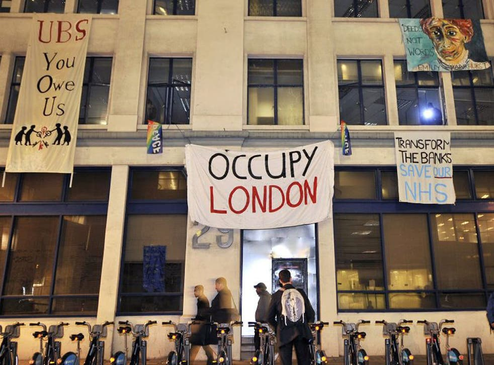 Occupy protesters hang banners from an empty office block owned by UBS bank in London