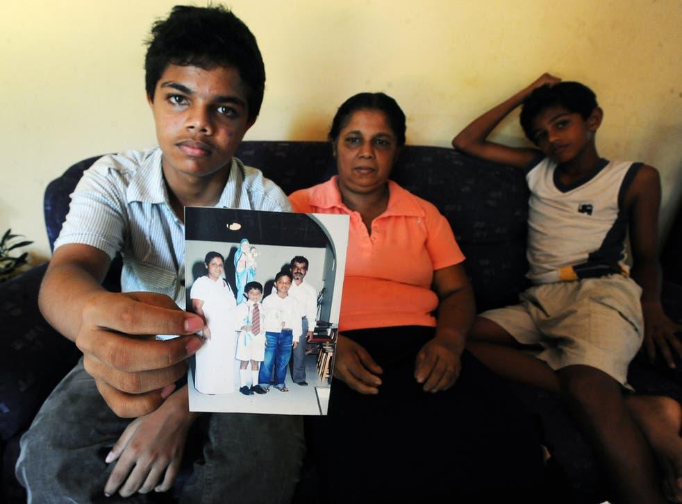 Harith Eknaligoda holds a picture that includes his missing father, the Sri Lankan journalist Prageeth Eknaligoda