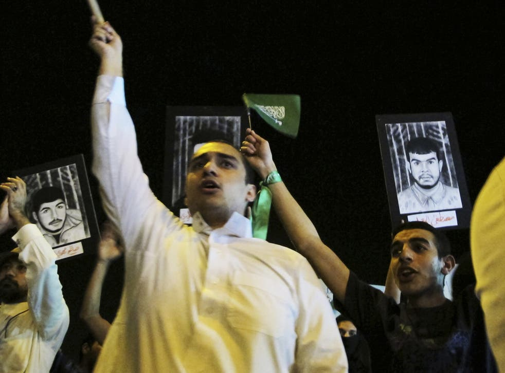Shias hold flags and portraits of prisoners in Qatif earlier this year