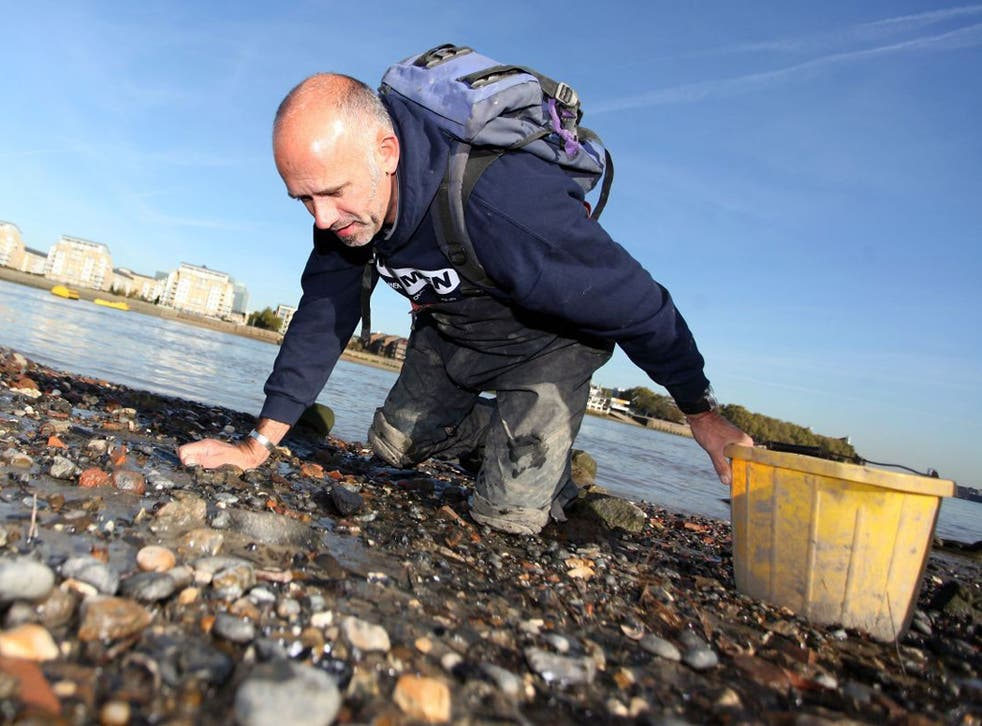 Steve 'Mud God' Brooker is pictured mudlarking for artefacts on the beaches of the river Thames at low tide.