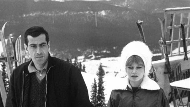 Actress Brigitte Bardot wraps up warm to take a stroll on the slopes with the director Roger Vadim in 1961