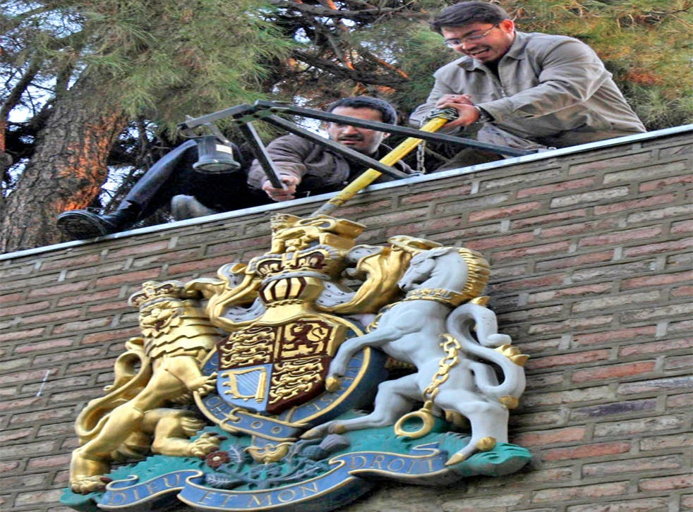 Protesters tear down the royal emblem
