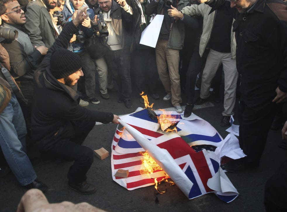 Iranian protesters setting fire to the flags of Britain, Israel and the US on Tuesday