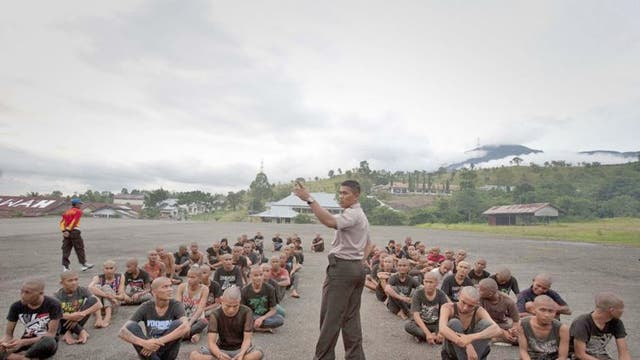 A police officer lectures a group of detained Indonesian punks at a police school in Aceh Besar in Aceh province