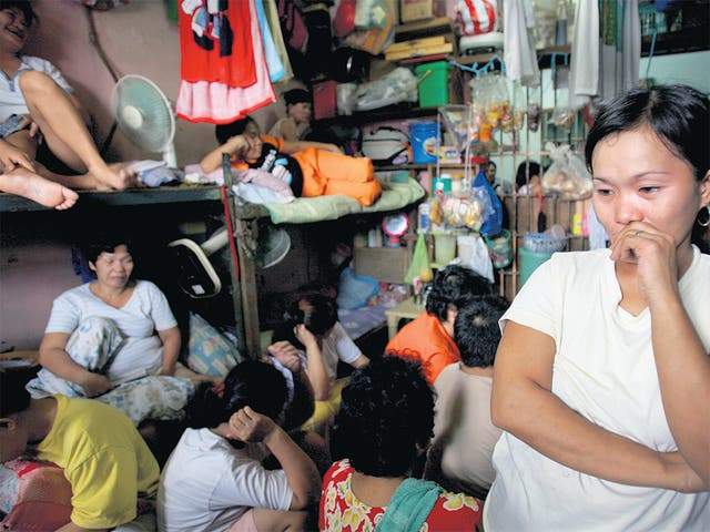<p>Overcrowded and insanitary: A woman stands in the corner of a female cell, where several dozen inmates are crammed in, at the Navotas Municipal Prison in Manila, Philippines</p>