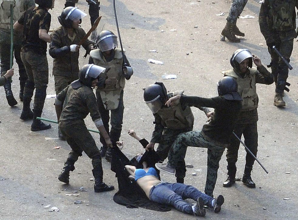 <p>A woman is attacked by police officers in Tahrir Square, revealing her bra at one point</p>