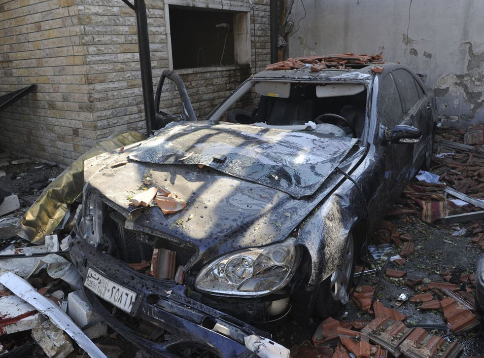 A damaged car is seen where a car bomb blew up at security sites in Damascus