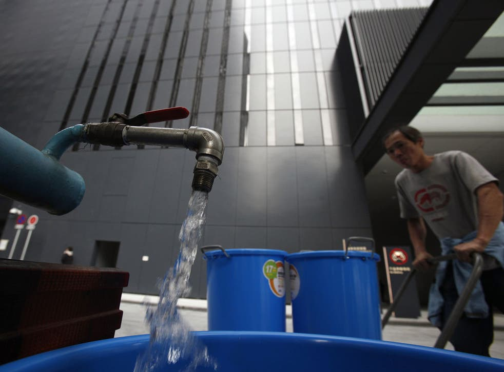 A worker transports buckets of clean water from a water tanker into Hong Kong's new government headquarters