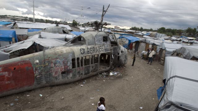 A girl walks past an abandoned helicopter at a camp in Port-au-Prince, which was set up for people displaced by the 2010 earthquake. More than half a million Haitians are still homeless
