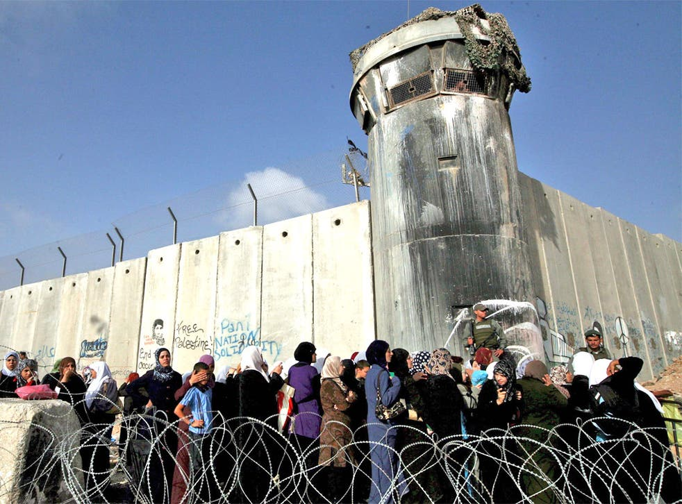 Palestinians wait to pass a checkpoint outside the West Bank city of Ramallah