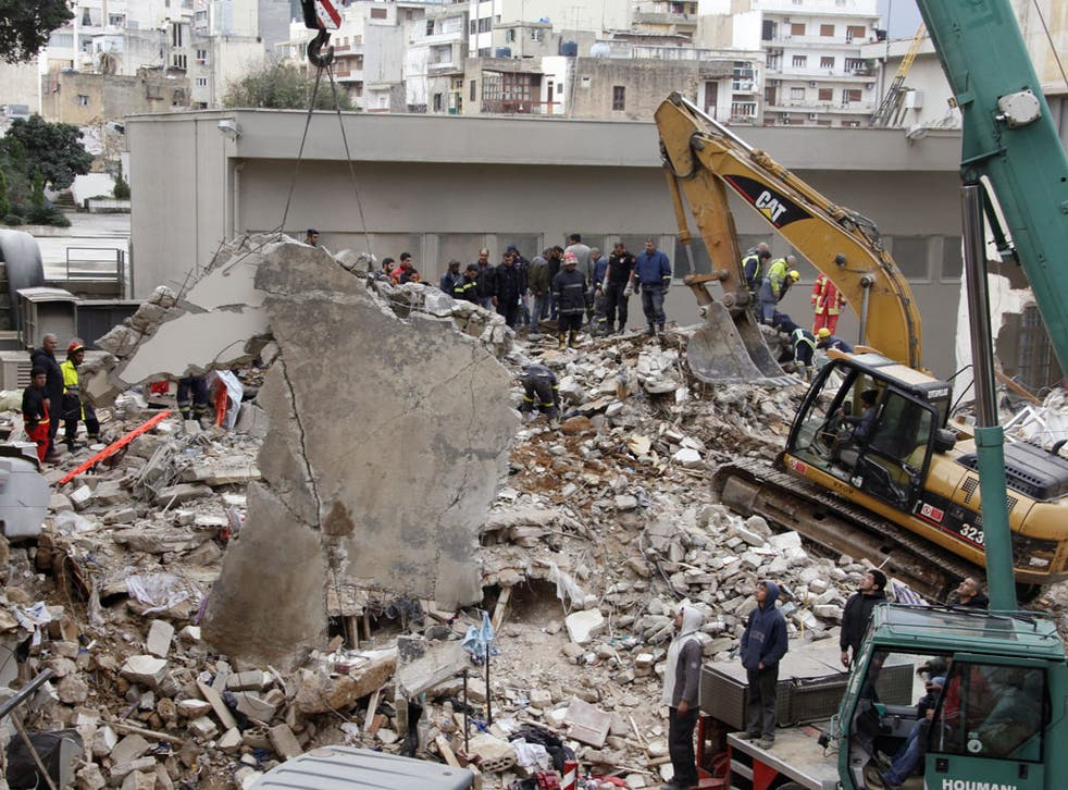 Rescue workers remove rubble at the site of the collapsed building in Beirut