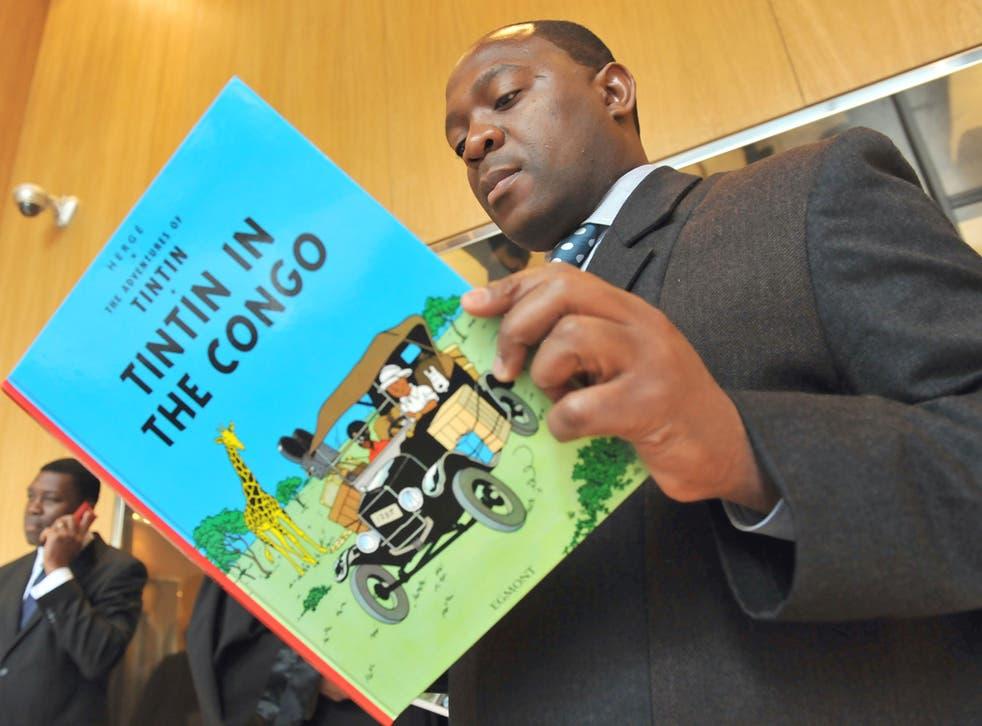 Bienvenu Mbutu Mondondo with a copy of the book he tried to ban