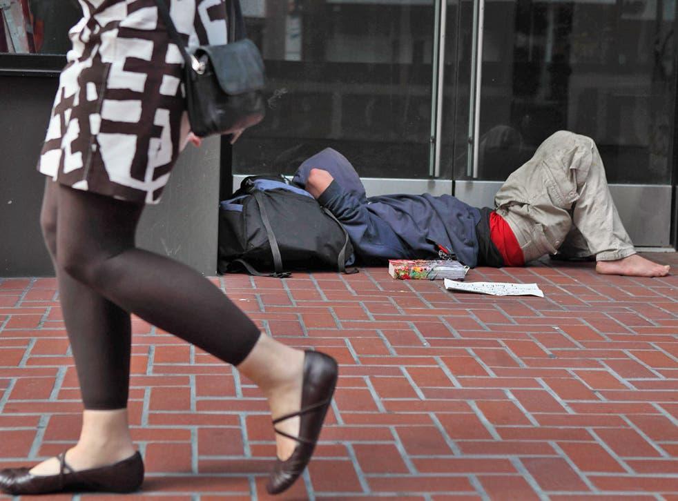 A homeless man sleeps in the street