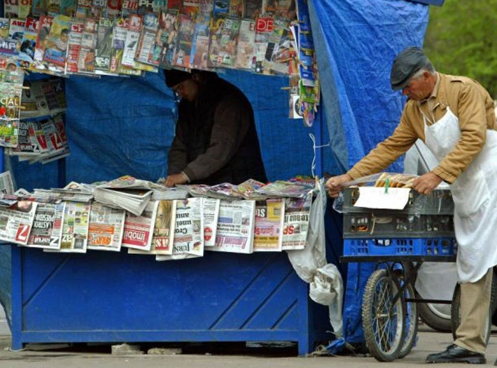 A Romanian pretzel seller arranges his wares near a newsvendor's stall in Bucharest