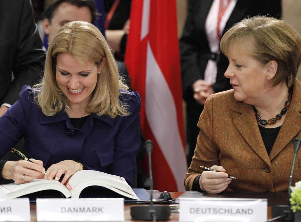 Angela Merkel (right) and Danish Prime Minister Helle Thorning Schmidt sign the EU fiscal compact in Brussels yesterday