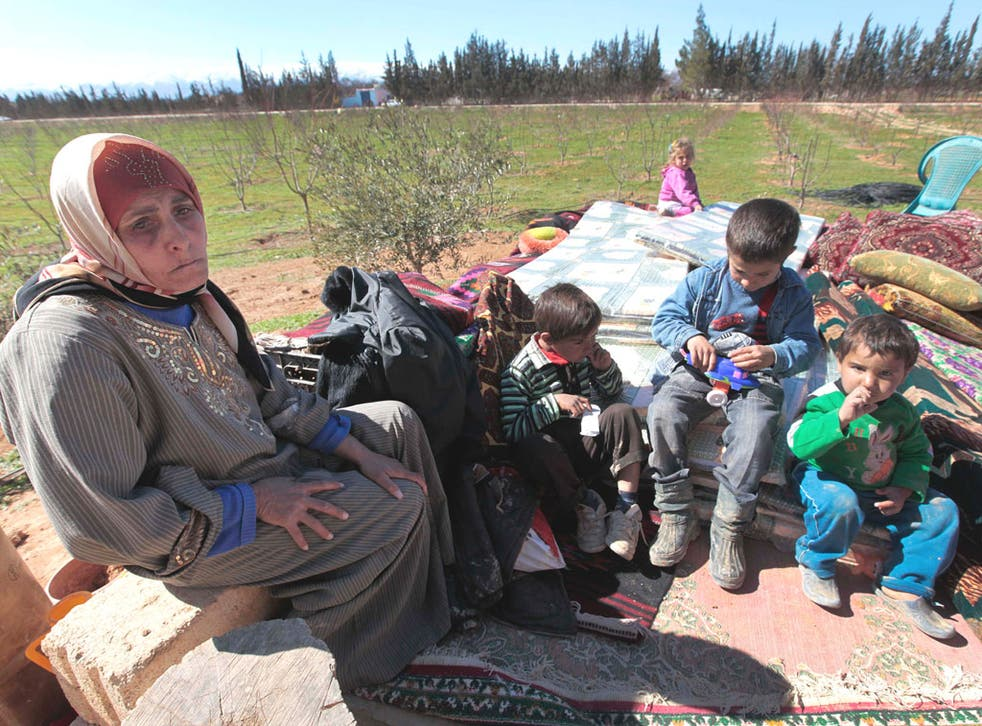 Syrian refugee Hassana Abu Firas with her family at the Lebanese- Syrian border village of Qaa. Up to 2,000 Syrians have poured across the border in the past two days