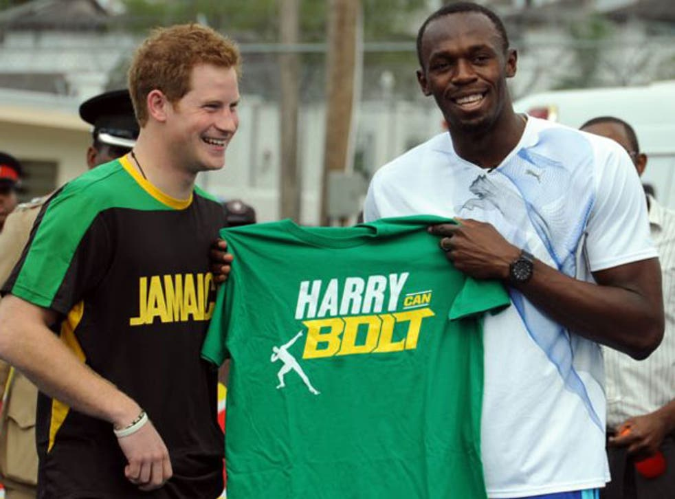 Prince Harry receives a T-shirt as a gift from Olympic sprint champion Usain Bolt