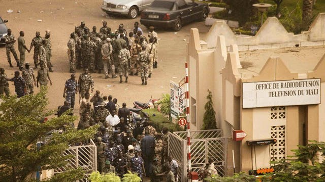 Malian soldiers and security forces gather at the offices of the state radio and television broadcaster after announcing a coup d'etat