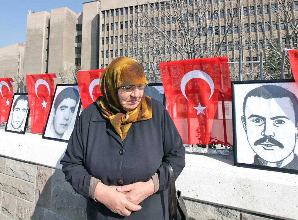 A woman stands in front of portraits of youths who were executed, died or disappeared in jails during military rule after Turkey's 1980 coup