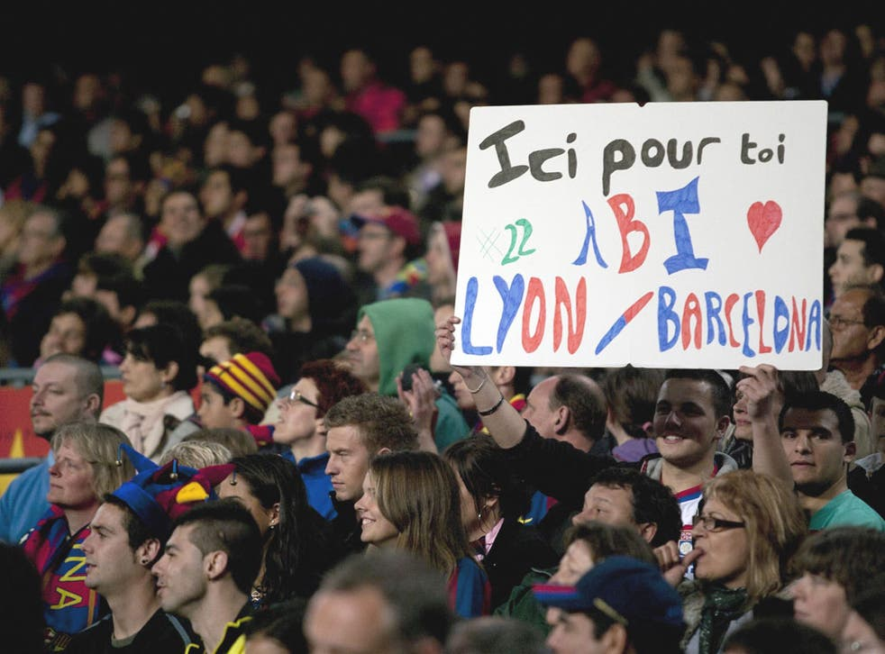 Barcelona fans hold a placard with a message of support for Eric Abidal, during their La Liga match  against Getafe at the Camp Nou