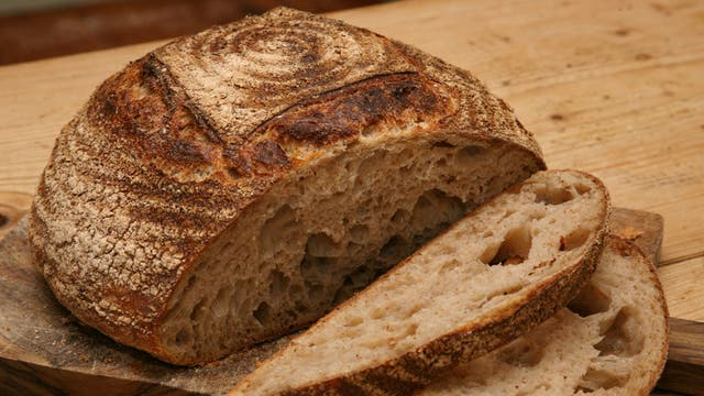 A golden-domed loaf of sourdough bread; its crunchy crust has an 'explosive quality'