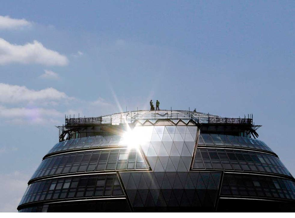 Workers install photovoltaic solar panels on the roof of London's City Hall. But demand for them has fallen