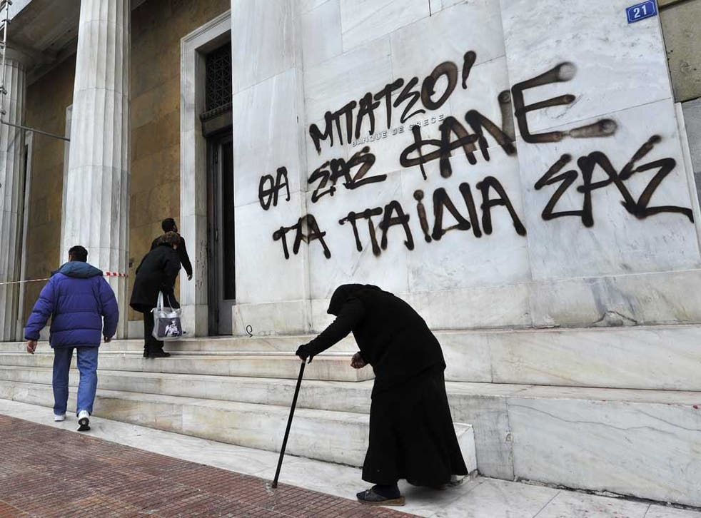Victims of austerity: A woman begs outside an Athens bank. The graffiti reads: 'Cops, your children will eat you'
