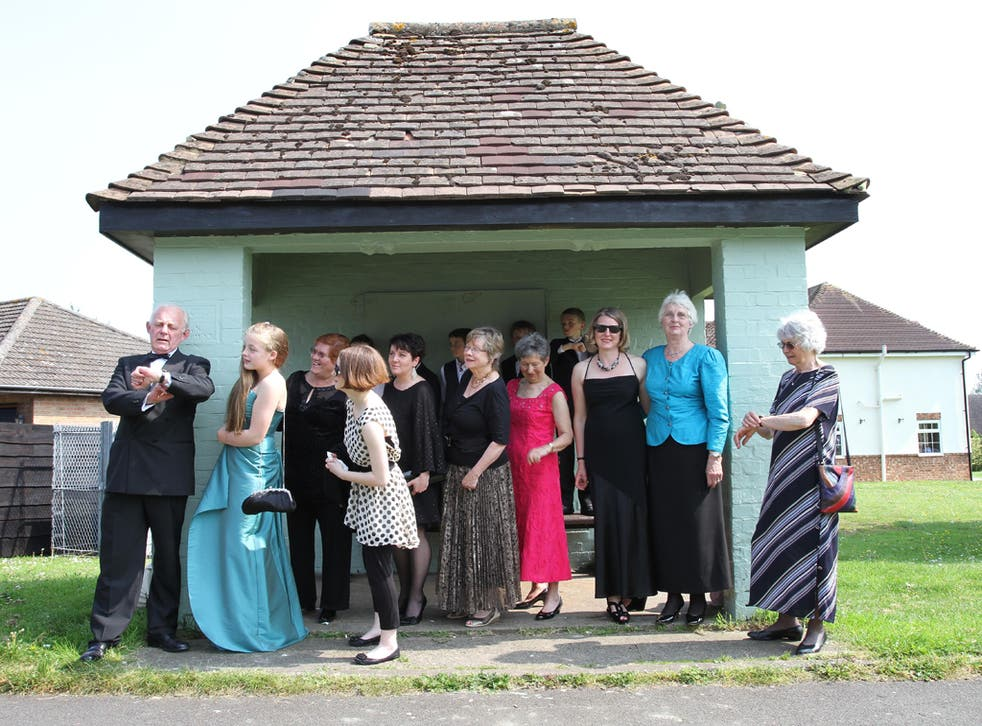 Residents of Kingston Bagpuize in Oxfordshire wait for buses to take them to the premiere