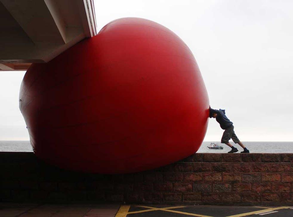 Kurt Perschke pushes a giant ball into Paignton's esplanade