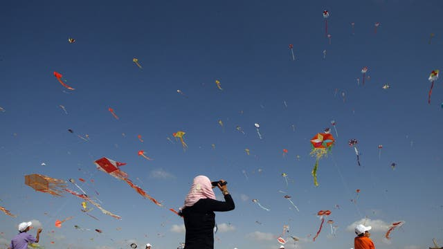 Palestinian children fly kites in the town of Beit Lahiya