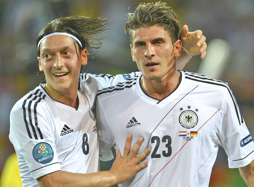 Mario Gomez (right) is congratulated by Mesut Ozil after scoring his and Germany's second last night